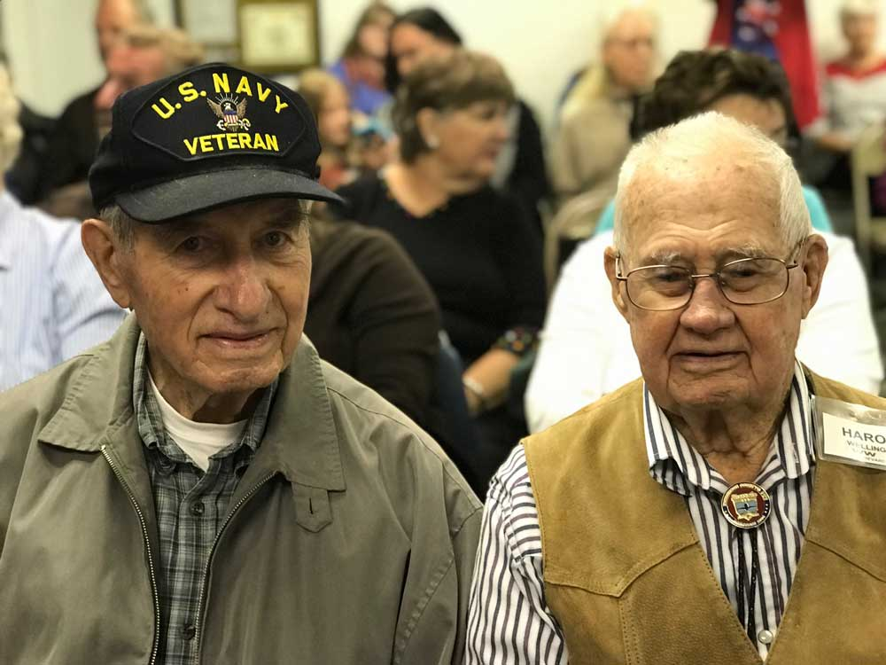 two veterans sitting in a crowd