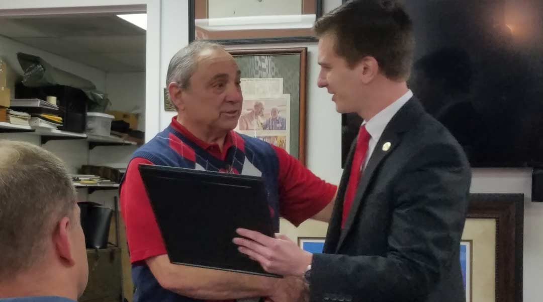 museum curator receives plaque from NC State Legislature