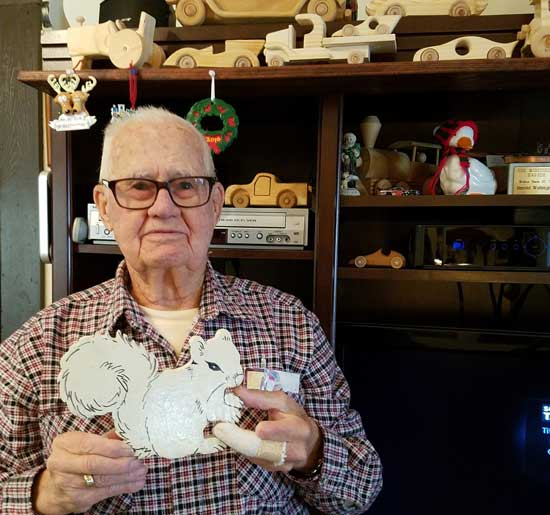 harold holding wood carved white squirrel