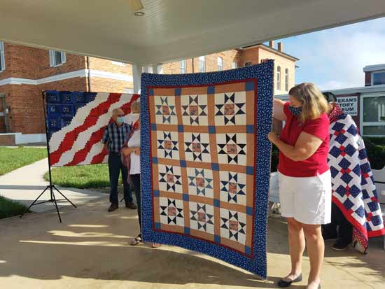 ladies holding valor quilt